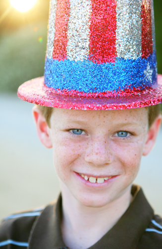 Freckle face boy with american flag uncle sam hat on 4th of July