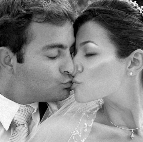 funny wedding portrait photograph of couple kissing close up